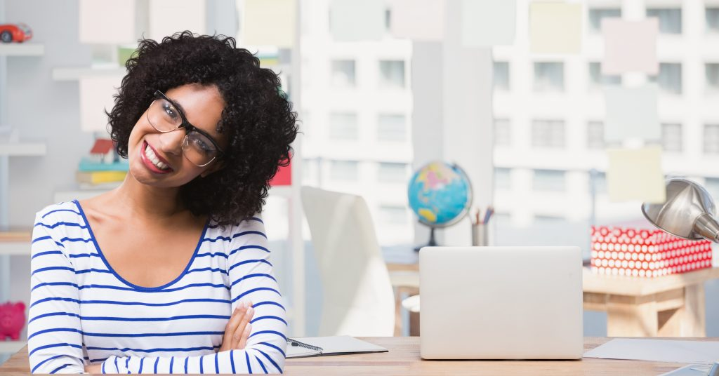 Portrait of woman in spectacles smiling against school background