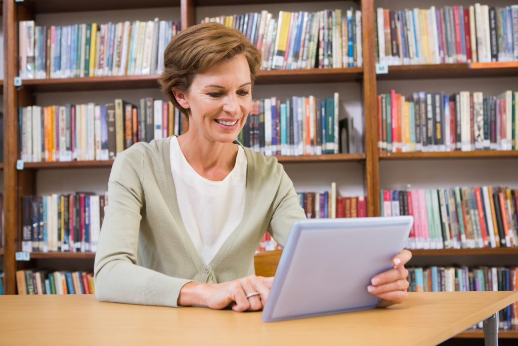Smiling teacher using tablet pc at library at elementary school